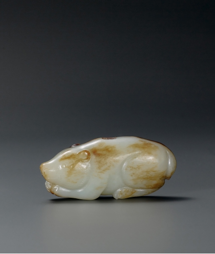 A FINELY CARVED PALE CELADON JADE RECUMBENT BEAR