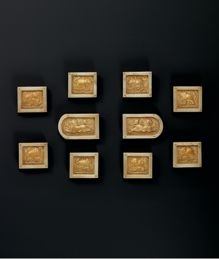 A FINE AND RARE SET OF TEN WHITE-JADE-MOUNTED GOLD 'LION' PLAQUES