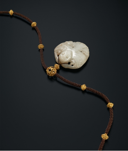 A FINELY CARVED WHITE JADE 'GARUDA' WITH 'FLORAL' GOLD BEADS NECKLACE